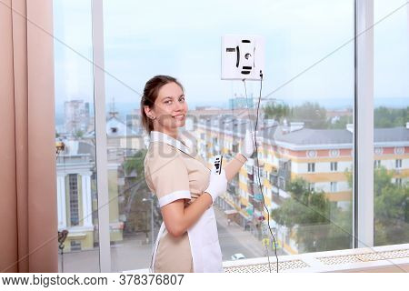 A Uniformed Maid Adjusts A Window Cleaner Robot On The Glass. Clean Windows. Photos In The Interior.