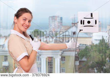 A Young Maid In Uniform Smiles And Sets Up A Window Cleaner Robot On The Glass. Clear Window. Photos