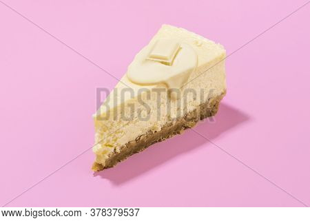 Cheesecake Slice With Melted White Chocolate Sauce And Creamy Filling, Isolated On Pink Seamless Bac