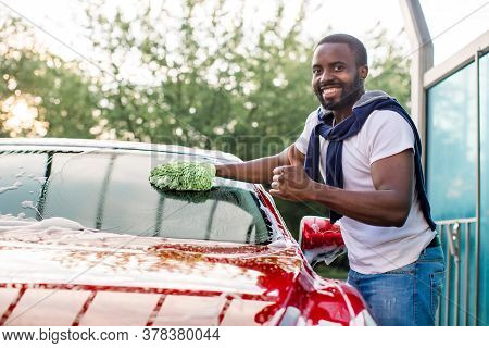 Outdoor Car Wash With Sponge And Foam. Car Washing. Smiling African Man Showing Thumb Up, Cleaning H
