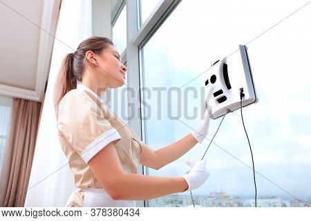 A Uniformed Maid Installs A Window Cleaner Robot On The Glass. Clean Windows. Photos In The Interior