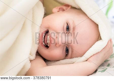 Soft Focused Portrait Of A Little Cute Boy Who Is Lying On The Bed Hidden In A Light Beige Blanket A