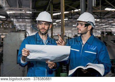 Factory Engineer Or Mechanical Worker With White Safety Helmet Holding The Manual And Checking On Pr