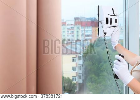 The Maid Installs A Robot Window Cleaner On The Glass. Clear Window. Photos In The Interior. The Con