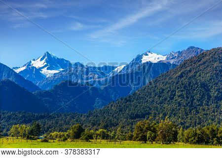 Wonderful summer day. The highest peak of New Zealand, Mount Cook and Mount Tasman is covered in snow and glaciers. Great fields, forests and hills. South Island of New Zealand