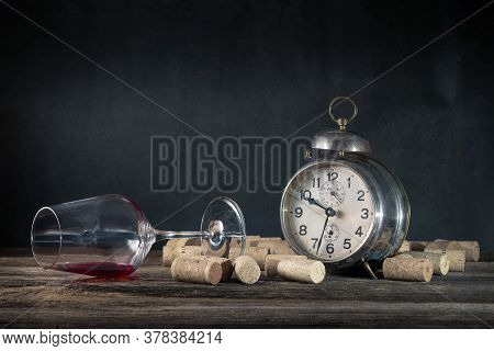 Empty Wine Glass Of Alcoholic Drink, Corks And Vintage Alarm Clock, Concept Of Alcoholism
