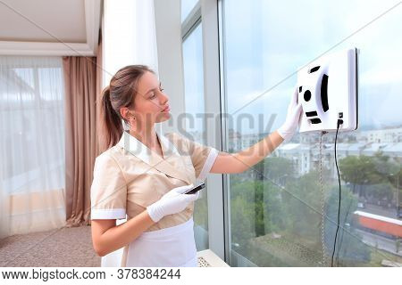 A Uniformed Maid Controls A Robot Window Cleaner. Clear Window. Photos In The Interior. The Concept