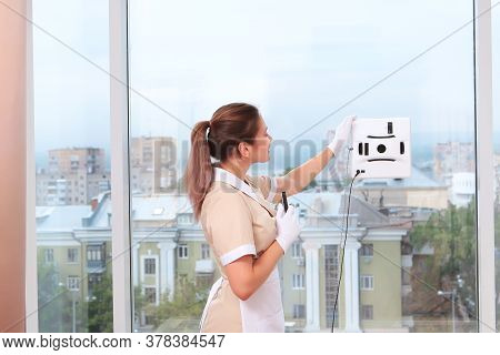 A Satisfied Uniformed Maid Remotely Controls A Window Cleaner Robot. Room Service. Cleaning In The H