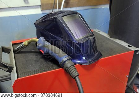 Tools For Welding. Welder's Protective Mask, Electrode For Electric Arc Welding Lies On The Box For