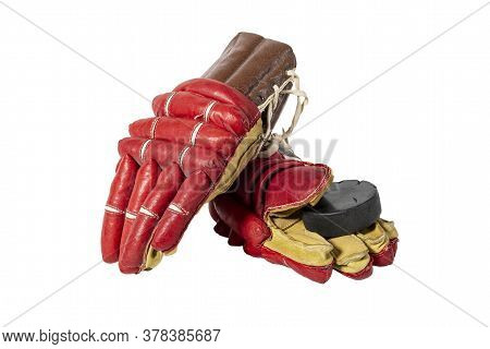 Old Red Hockey Gloves For Goalkeeper. Isolated Over White Background. Hockey Puck. The Concept Of Th