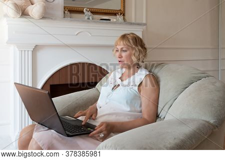 Beautiful Fifty Year Old Woman Sitting In A Chair And Looking At A Laptop
