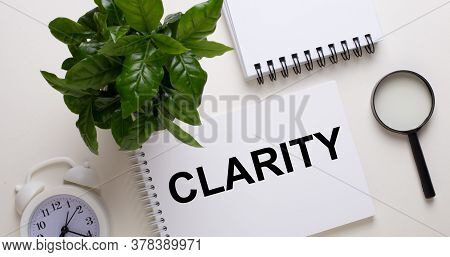 The Word Clarity Is Written On A White Notepad Next To A White Alarm Clock, A Magnifying Glass, And