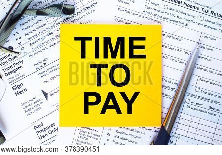 Tax-filling Concept. Text Time To Pay On Note Paper With The U.s Irs 1040 Form,pen And Glasses
