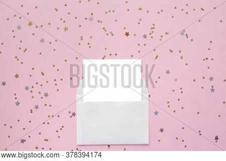White Blank Card In White Envelope On Pink Background With Golden Confetti. Holiday Mockup. Top View