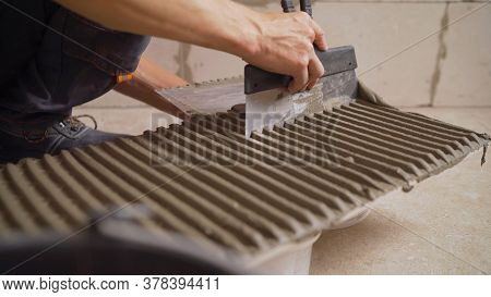 The Master Smears The Tiles With Glue. The Master Tile Smears The Mucilage Solution On The Marble Ti