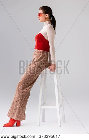 Side View Of Fashionable Girl In Beige Trousers And Red Corset On Turtleneck Leaning On Stool On Gre
