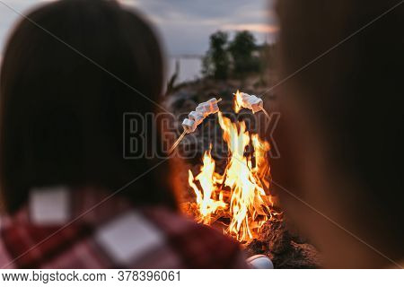 Selective Focus Of Puffy Marshmallows On Sticks Near Bonfire And Couple