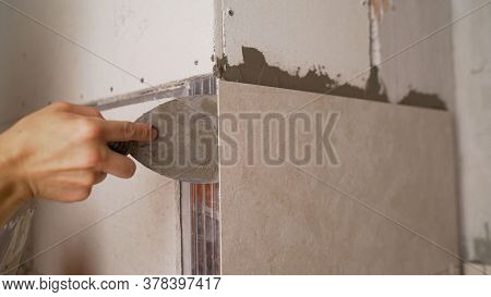 The Bathroom Tiles Were Glued To The Wall. Master Glues Bathroom Tiles. The Tiles Were Glued To The