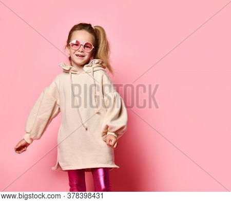 Glamorous Little Girl In Pink Glasses Posing Confidently In A Pale Pink Sweatshirt And Glossy Leggin