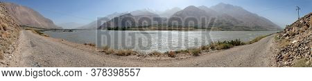 Panj River And Hindukush Mountains Panoramic View. Panj Is Upper Part Of Amu Darya River. Tajikistan