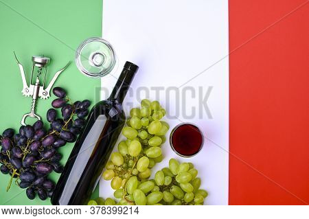 A Bottle Of Wine, Grapes, And The Flag Of Italy Close-up. Country Symbol Backdrop. The Concept Of Ha