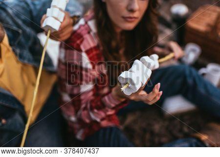 Selective Focus Of Puffy Marshmallows On Sticks Near Couple