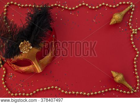 Christmas Red Background With Masquerade Mask, Golden Beads, Confetti And Christmas Decoration. Flat
