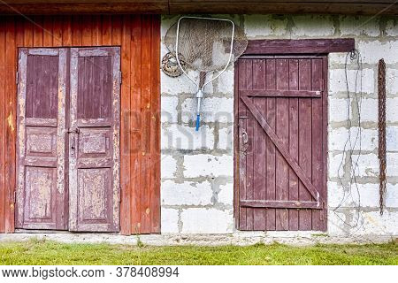 Shed With Old Wooden Doors And Fishing Tackles Hinged On Wall.