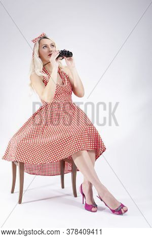 Full Length Portrait Of Caucasian Blond Girl Posing In Pin-up Style. Sitting On Chair With Binocular