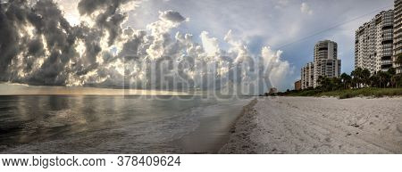 Panoramic Sun Peeks Through The Clouds Over The Ocean At Sunset In Naples, Florida