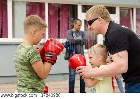 Komsomolsk-on-amur, Russia - July 21, 2018. Kickboxing Coach Shows The Boy How To Make Punch In Spar