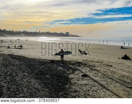 Surfer In Wet Suit Holding A Surfboard On The Beach. Surfer Going To The Water During Sunset Time, O