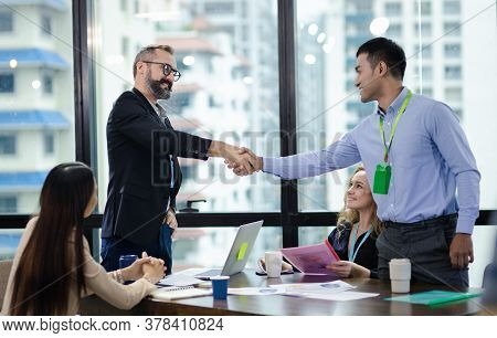 Young Manager Handshake With New Employee. Businessmen Making Handshake In Meeting Room, Congratulat