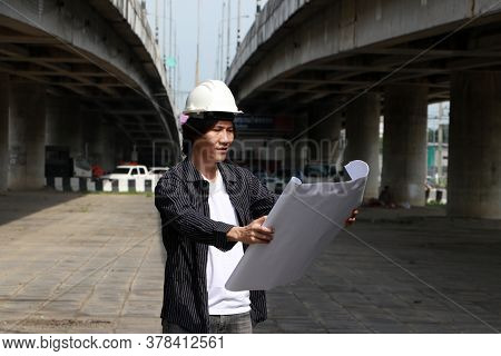 Civil Engineer Man With White Helmet, Standing And Looks At The Project Drafts While On Parallel Exp