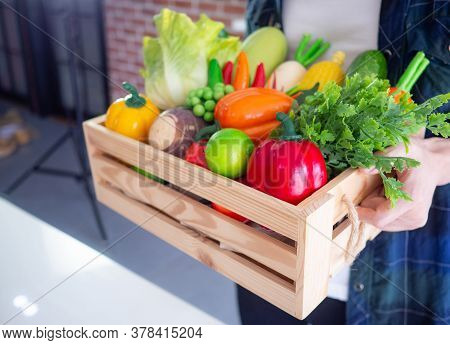 Close-up Photo Of Hands Young Man Is Holding A Basket Box Wooden With Colorful Vegetables And Fruits