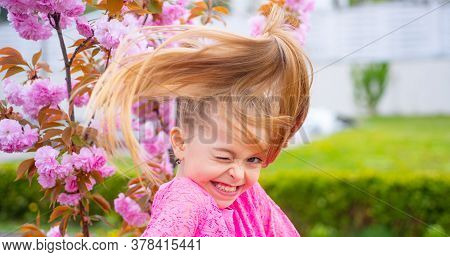 Crazy Spring Teenager Girl In Fragrant Pink Flowers In Summer Blossom Park. Comic Grimace, Funny Emo