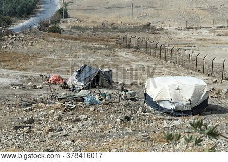 Bedouin Houses In The Desert Near Dead Sea. Poor Regions Of The World. A Indigent Bedouin Sitting At