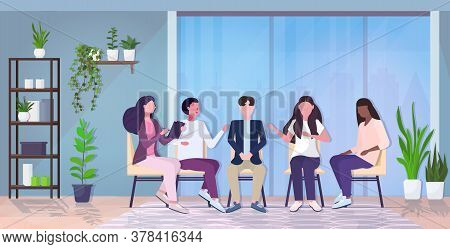 Female Psychologist Talking With Patients Group During Psychotherapy Session Treatment Of Stress Add