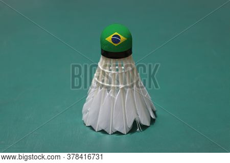 Used Shuttlecock And On Head Painted With Brazil Flag Put Vertical On Green Floor Of Badminton Court
