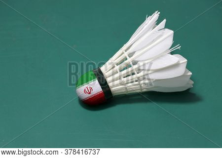 Used Shuttlecock And On Head Painted With Iran Flag Put Horizontal On Green Floor Of Badminton Court