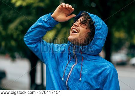 Cheerful Man Smiling Broadly, Wearing Blue Raincoat During Rain Outside. Handsome Male In Blue Rainc