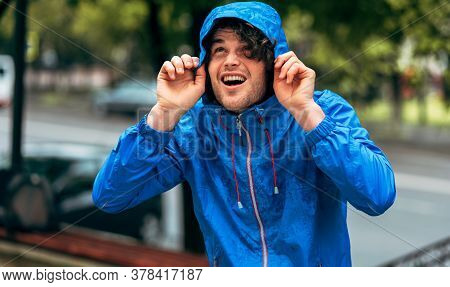 Image Of Man Smiling Broadly, Wearing Blue Raincoat During The Rain Outside. Handsome Happy Male In