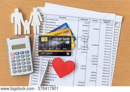 Family Model And Calculator On Bank Statement And Credit Card On A Wooden Table.