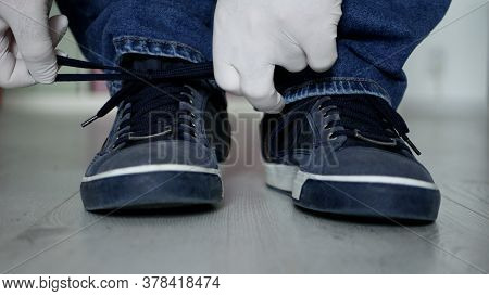 Man Preparing For A Walk Tying The Laces To His Sports Shoes Using Protection Gloves