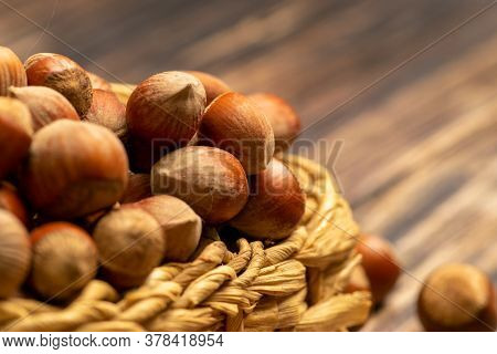 Hazelnuts In A Wicker Basket And Hazelnuts Scattered On A Wooden Background. Close Up.