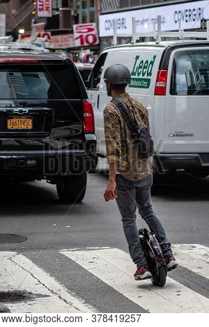 New York, Usa - June 6, 2019: A Man With An Electric Unicycle Moves Between Cars On A Street In Manh