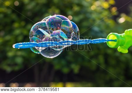 Close-up Of A Beautiful Colorful Soap Bubbles Shimmer And Glow In The Rays Of The Setting Sun On A G