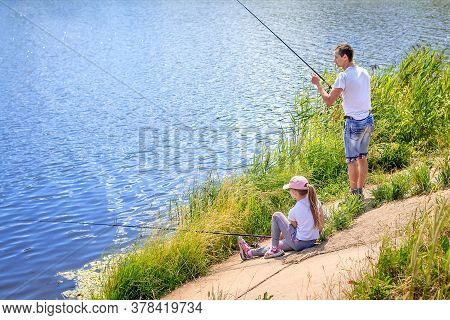 Daughter With Father Sit On The Shore Of Lake With Fishing Rods And Catch Fish. Concept Of Outdoor H