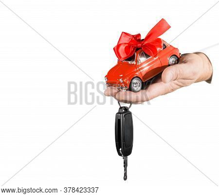 Red Car With Bow And Key On Dealers Hand Isolated On White Background. Car Purchase Concept