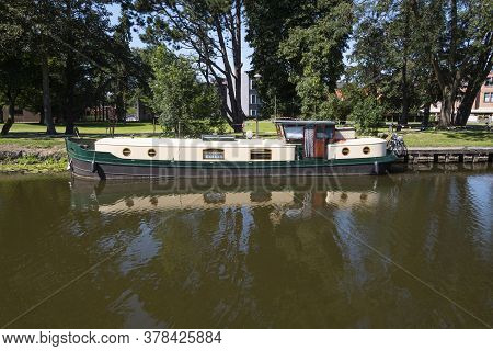 Lokeren, Belgium, Houseboat Moored On The Rippling Water Of The River Durme